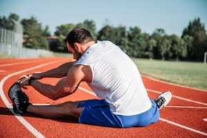 Athletic Caucasian man stretching his leg on a track