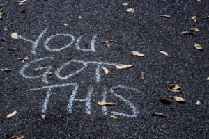 "The phrase ""you got this"" written in chalk on black pavement"