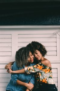 Two black women embracing each other and smiling