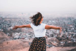 Woman holding arms wide open at high point overlooking city