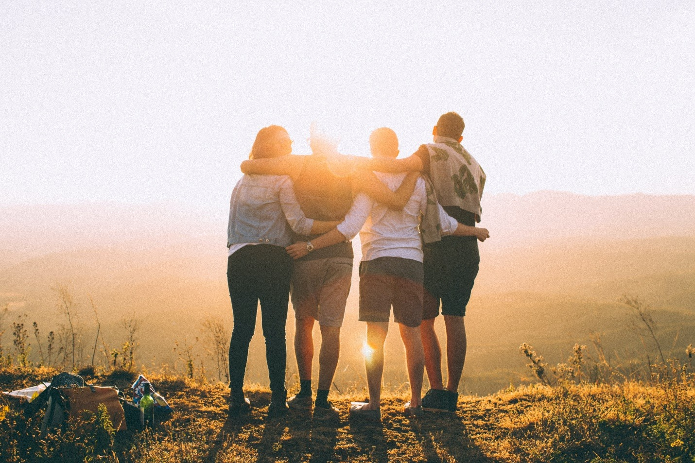 Group of friends hold up hands on the peak of mountain
