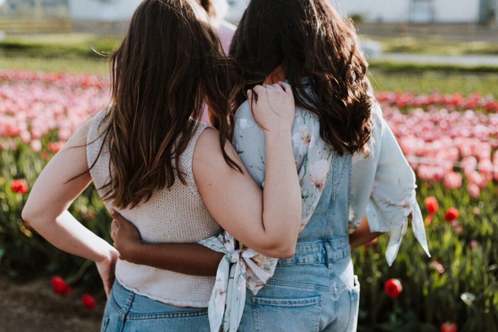 Rear View Of Women Walking Arm Around Outdoors