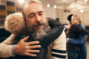 Old man hugging boy