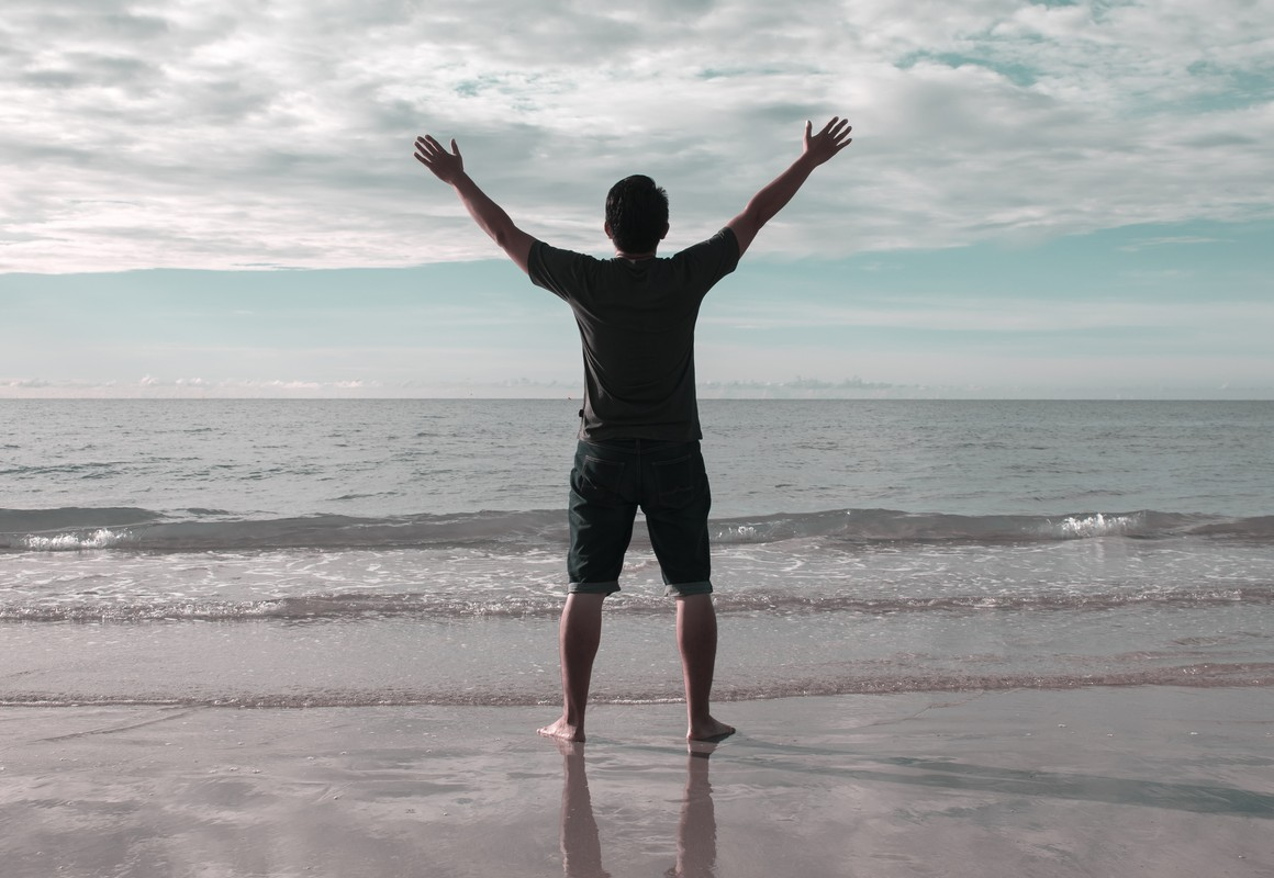 excited young man standing on beach with arms outstretched