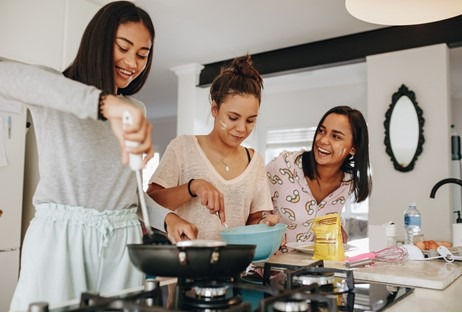 Three women cooking at a stovetop