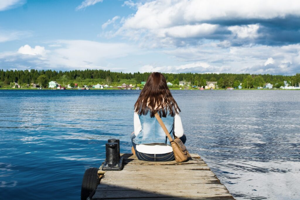 Young woman sitting on mooring near river and looking on shore