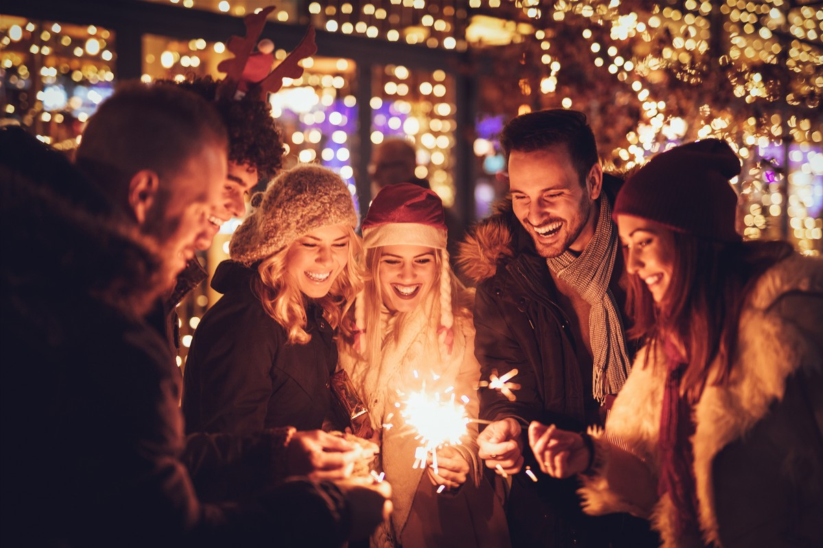 Three couple with sparklers enjoying Christmas outdoor party