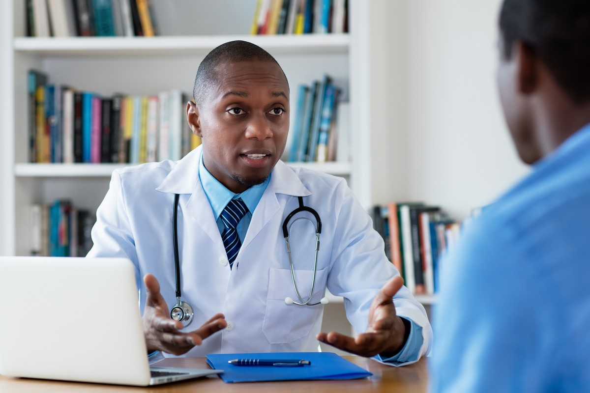 African american male doctor talking male patient