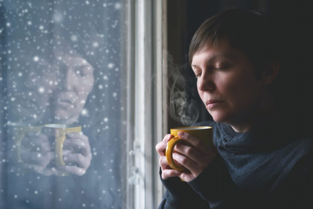 Lonely woman drinking cup of coffee by the window