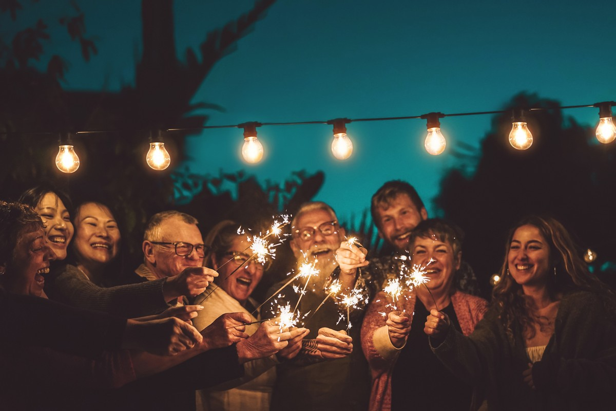 Group of people with different ages celebrating with sparkler at night party outdoor