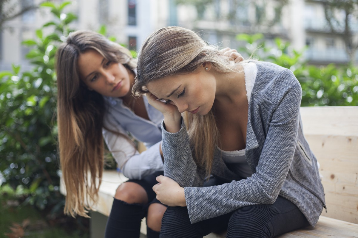 Woman comforting to a sad depressed friend who needs help