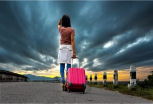 Woman with pink suitcase looking up at a stormy sky