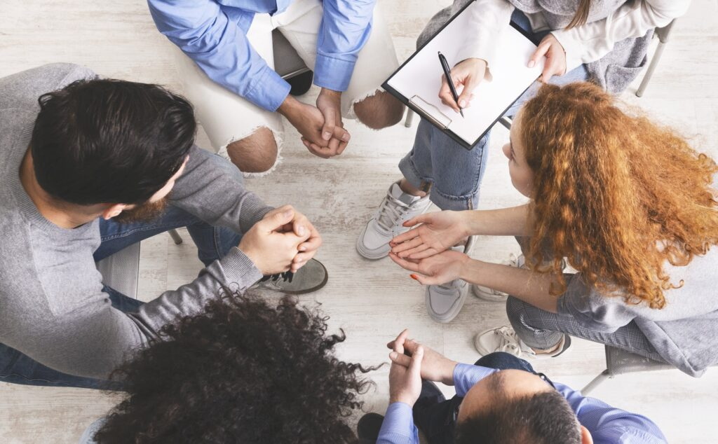 Diverse people discussing their problems with others seated in circle