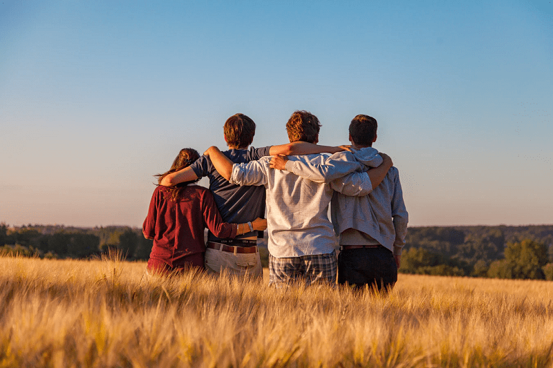 four people enjoying a group hug in a field