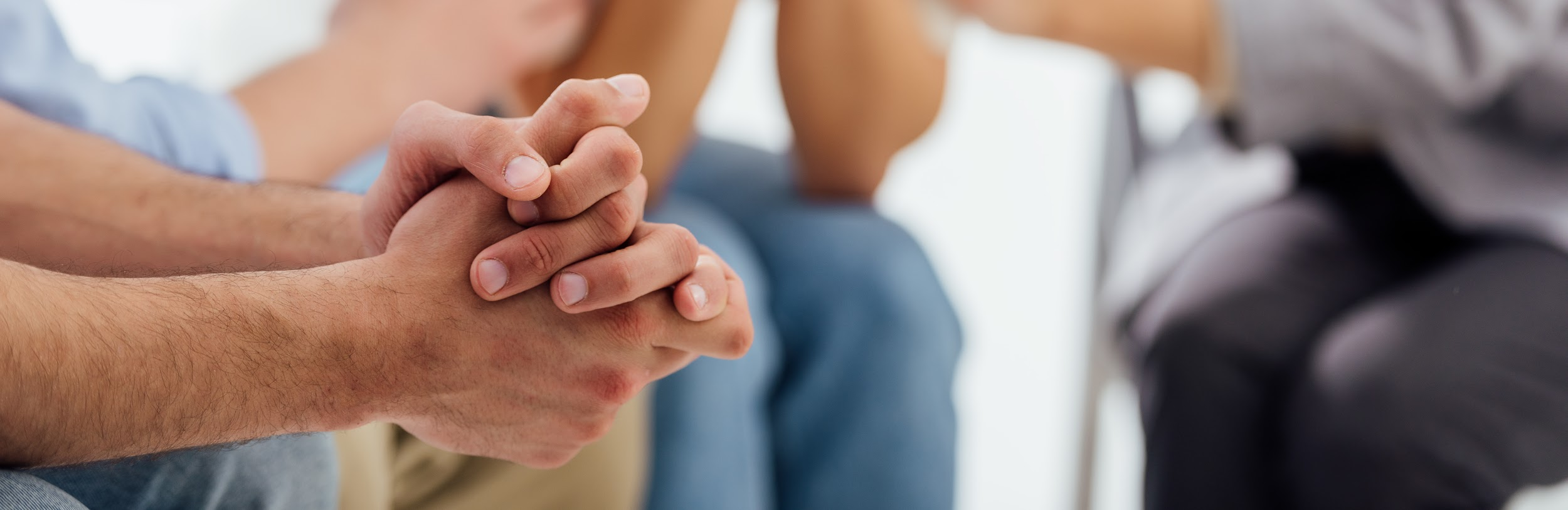 panoramic shot of hands of man during group therapy session