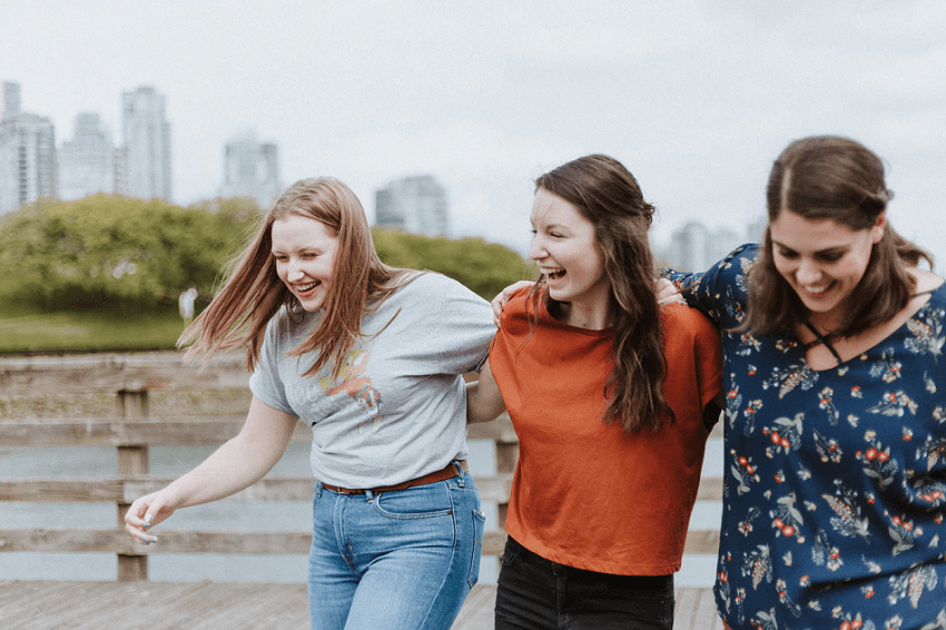 Three women friends standing arm in arm laughing and smiling