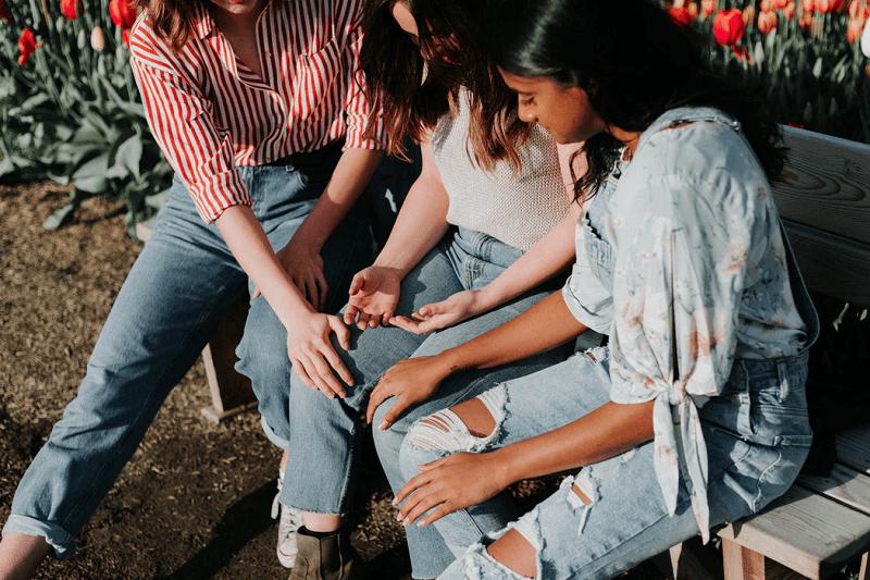 three women sitting on gray wooden bench