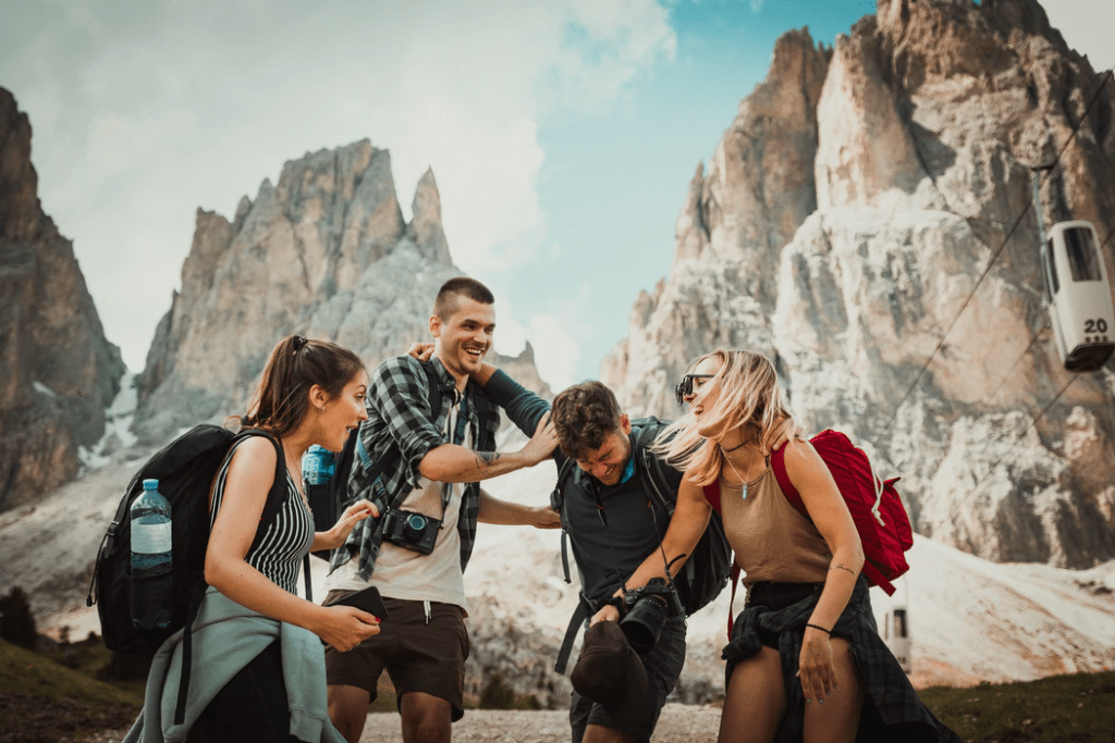 A group of four smiling friends at a canyon setting on a holiday