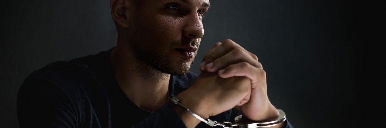 Man in handcuffs in dark room